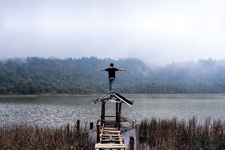 Man standing on gazebo by lake against sky