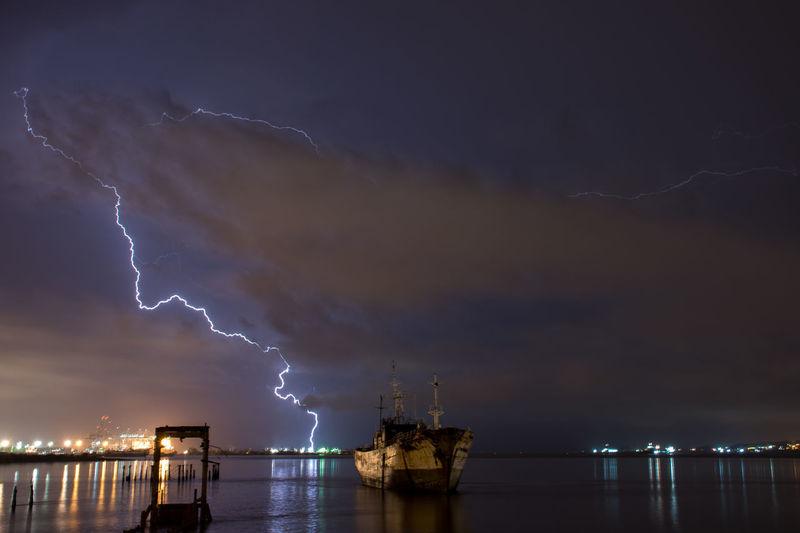 Lightning over sea against sky at night
