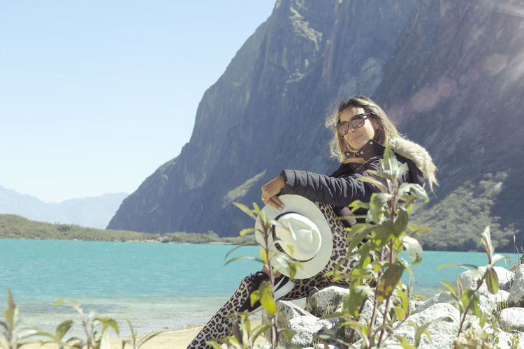 Portrait of woman by sea against mountains