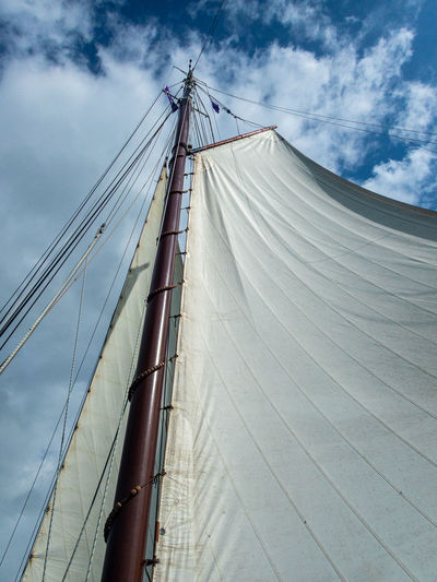 Low angle view of sailboat on bridge against sky