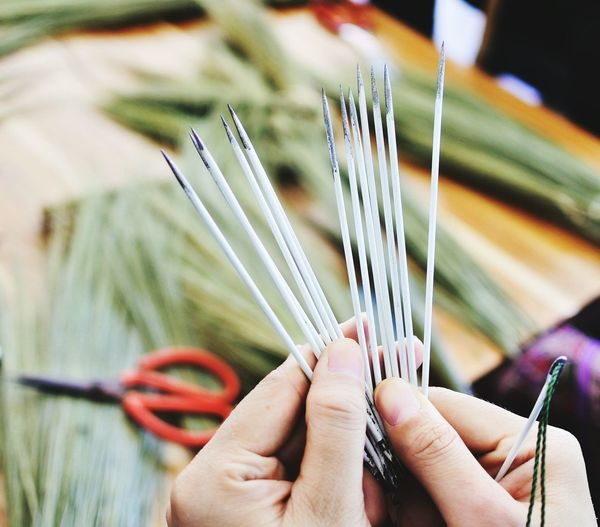 Close-Up Of Hands Holding Sewing Needles