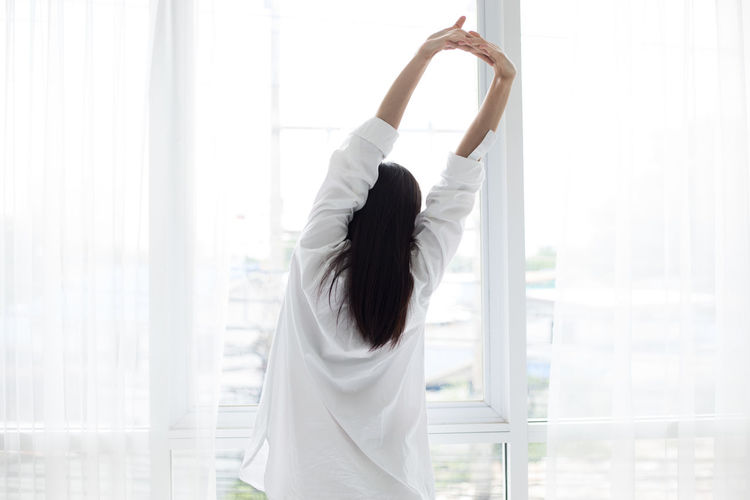 Woman Stretching Hands Against Window At Home