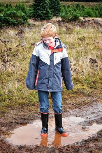 Full Length Of Boy Standing In Puddle