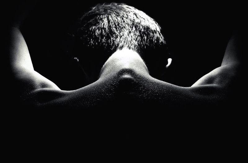 Rear view of shirtless man in darkroom