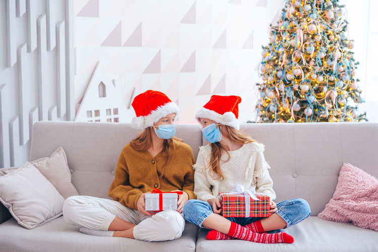 Full length sisters wearing mask sitting on sofa at home