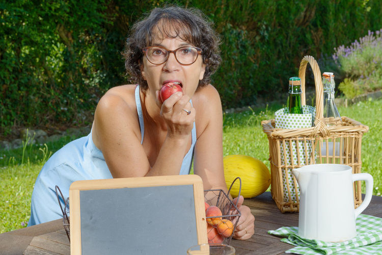 Portrait Of Woman Eating Fruit In Yard