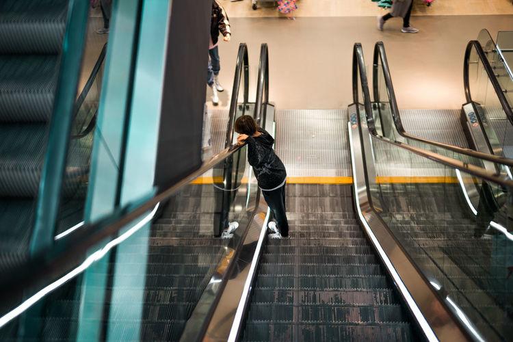 High angle view of boy standing on escalator