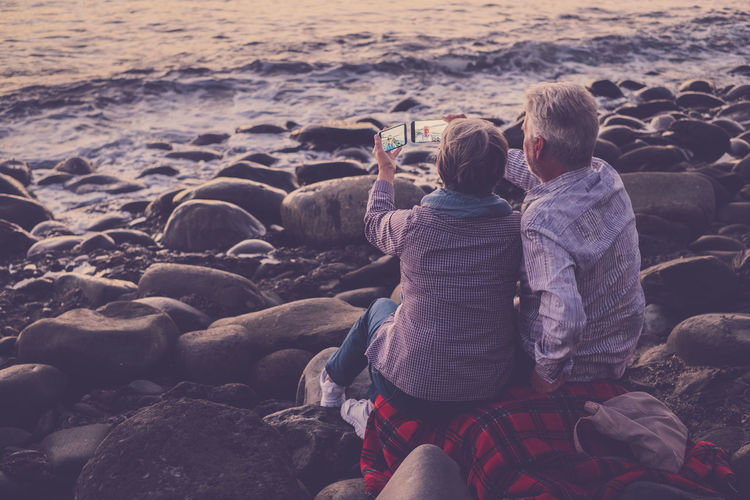 Rear View Of Couple Taking Selfie From Mobile Phones At Beach