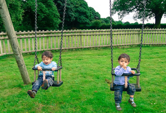 Twin boys playing on the swings with different reactions, one loves it and is really enjoying himself, the other is unsure. Aged 2 Years Boys Children Children Playing Differences  Different Emotions Different Reactions Enjoyment Happiness Pensive Playground Playing Reaction Sucking Thumb Swinging Swings Twins Two Is Better Than One