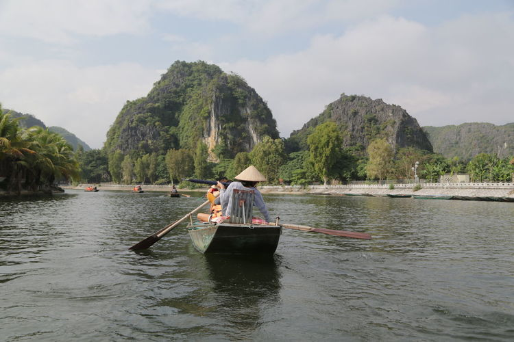 People on boat in river against sky