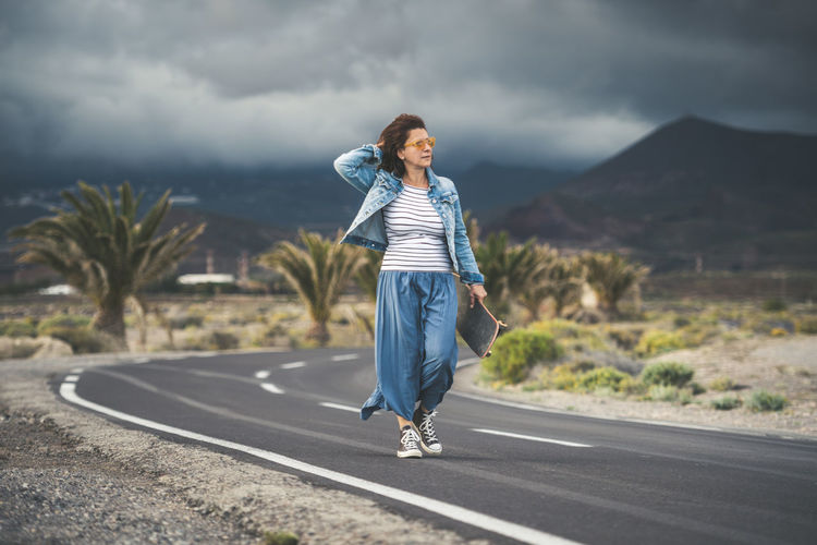Full Length Of Woman Walking On Road Against Cloudy Sky