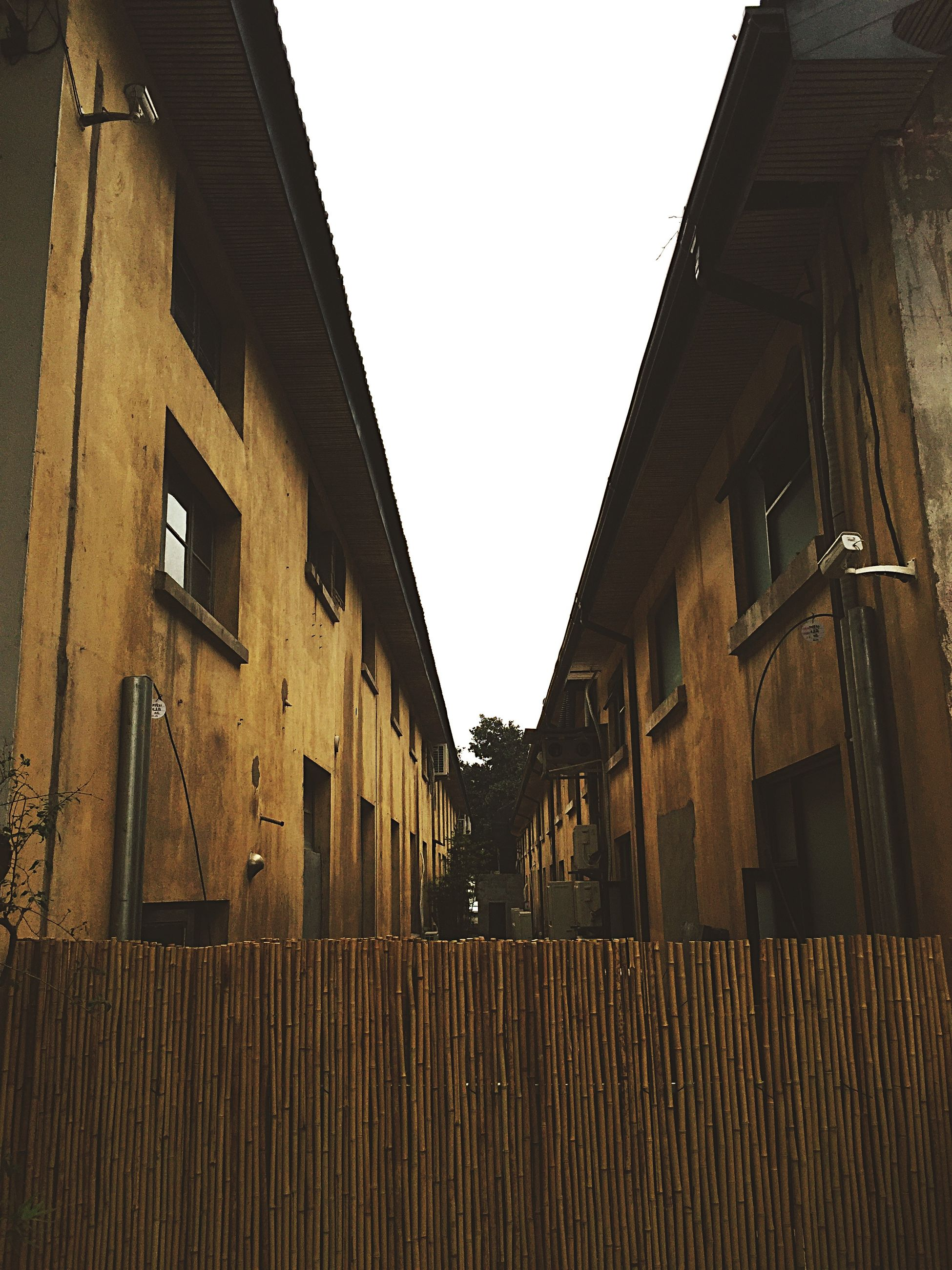 architecture, built structure, building exterior, clear sky, low angle view, residential building, building, residential structure, window, house, day, city, outdoors, no people, sky, old, sunlight, copy space, the way forward, diminishing perspective