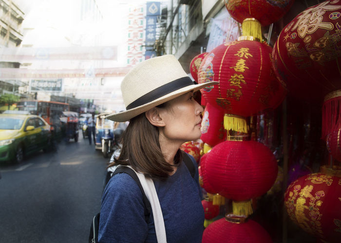 Mid adult woman looking at paper lanterns in city market