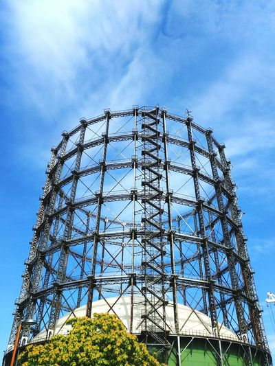 Low angle view of gasometer schoneberg against sky