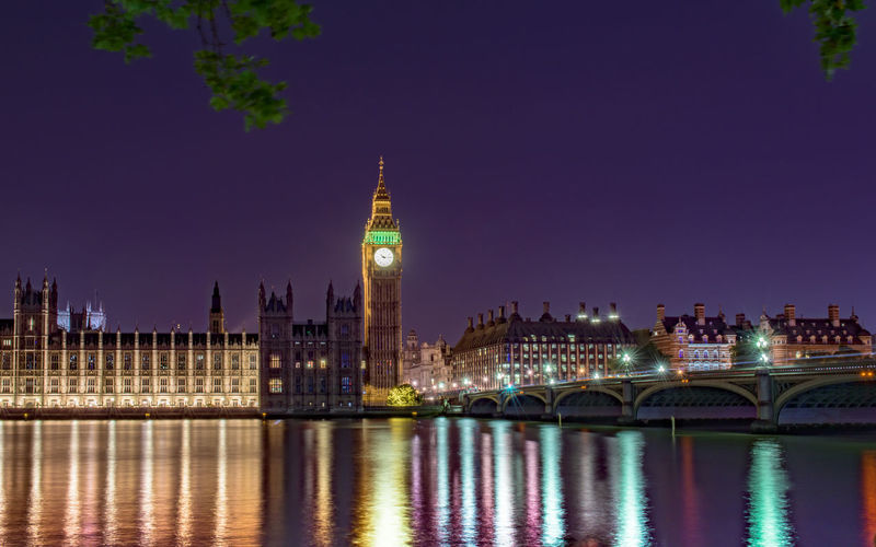 Colorful lights falling by westminster bridge over thames river at night