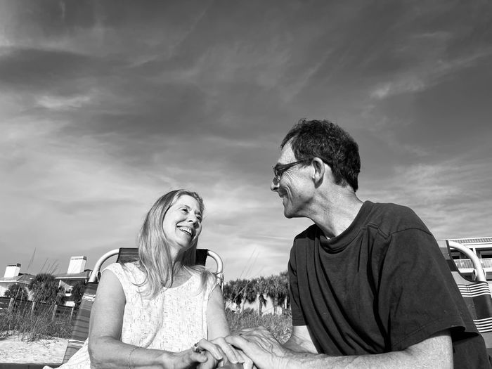 Senior man and senior woman laughing and  looking with affection at one another as they sit  outside