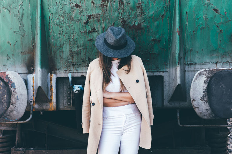 Young woman wearing hat standing against locomotive