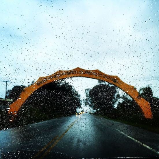 Arch Over Road Against Sky On Rainy Day Seen From Car Windshield