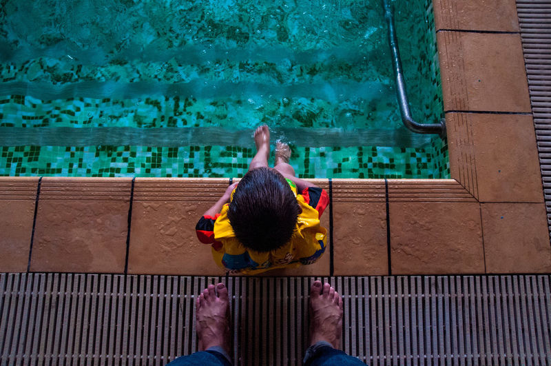 Low section of father standing by son sitting at poolside