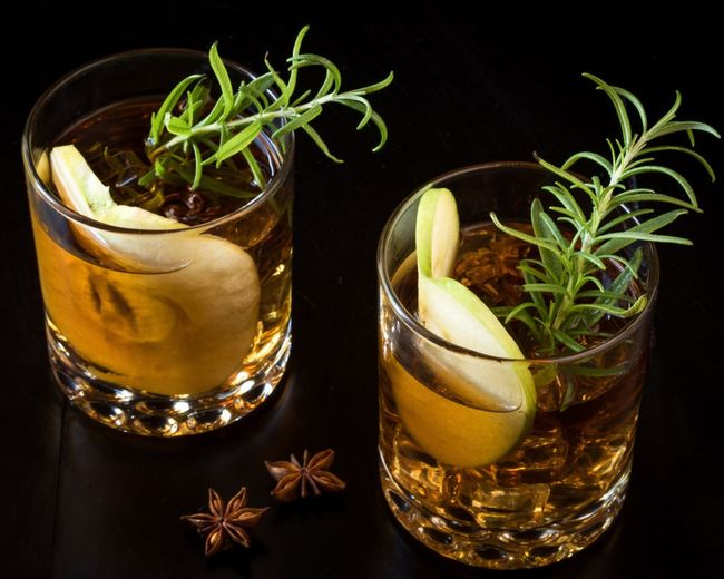 Close-up of fancy cocktails with apples and rosemary