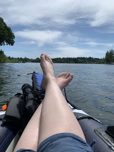 Low section of person relaxing on lake against sky