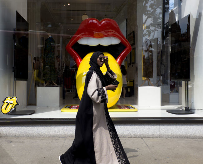 A woman dressing an Abaya Muslim dress walking in front of a shop display window celebrating The Rolling Stones concert in Oxford Street on 23rd May 2018 in London, United Kingdom. Oxford Street and Regent Street are well known for the captivating shop window design. London Streetphotography Oxfordstreet Shopping Shop Shopper Muslim Multiculturalism Islam TheRollingStones Tongue Mickjagger