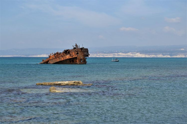 Rusty hulk of a half submerged shipwreck in shallow waters and rocks beneath the surface of the sea off the coast at Akrotiri, Cyprus CY Rust Beauty In Nature Cloud - Sky Day Deterioration Horizon Horizon Over Water Land Mode Of Transportation Motion Nature Nautical Vessel No People Outdoors Ruined Scenics - Nature Sea Ship Sinking Sky Tranquility Transportation Travel Water Waterfront