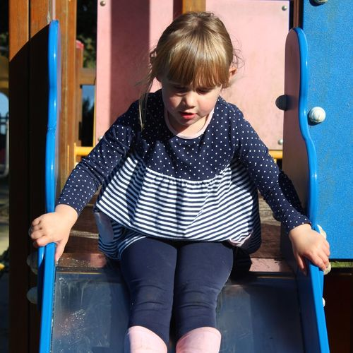Cute Girl Sitting On Slide