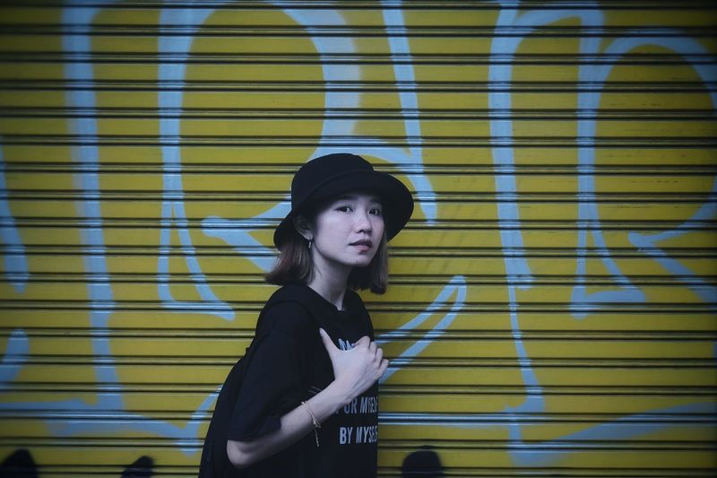 Portrait of woman standing against graffiti shutter