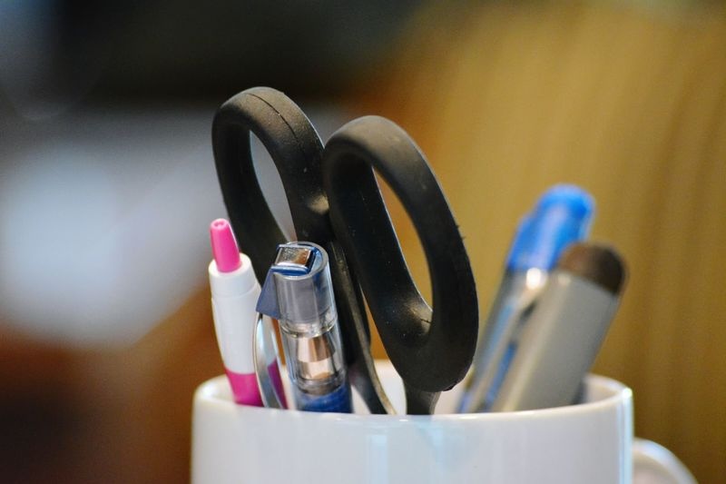 Close-up of pen and scissors in desk organizer