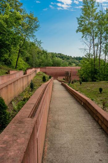 Footpath by bridge against sky