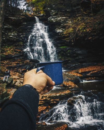 Optical Illusion Of Hand Filling Cup With Waterfall