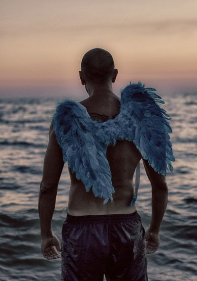 Rear View Of Shirtless Man With Costume Wings In Sea Against Sky
