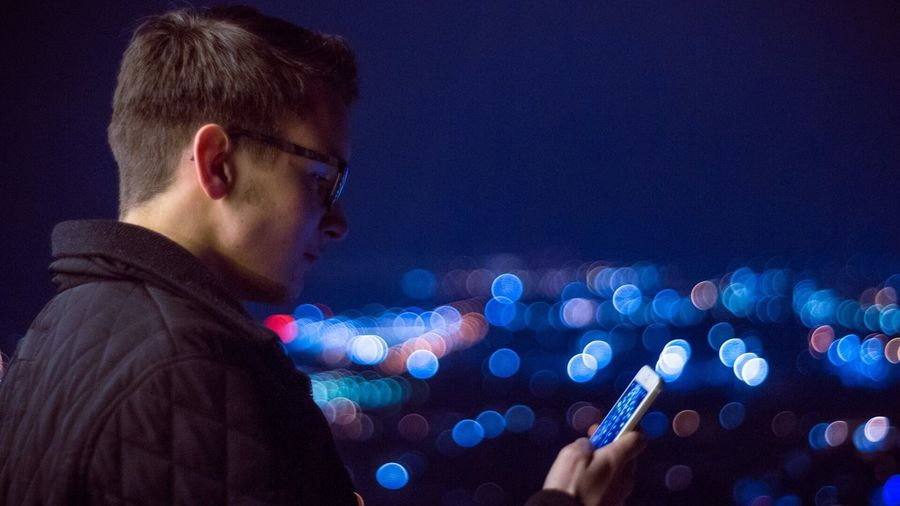 Side View Of Man Using Phone At Night