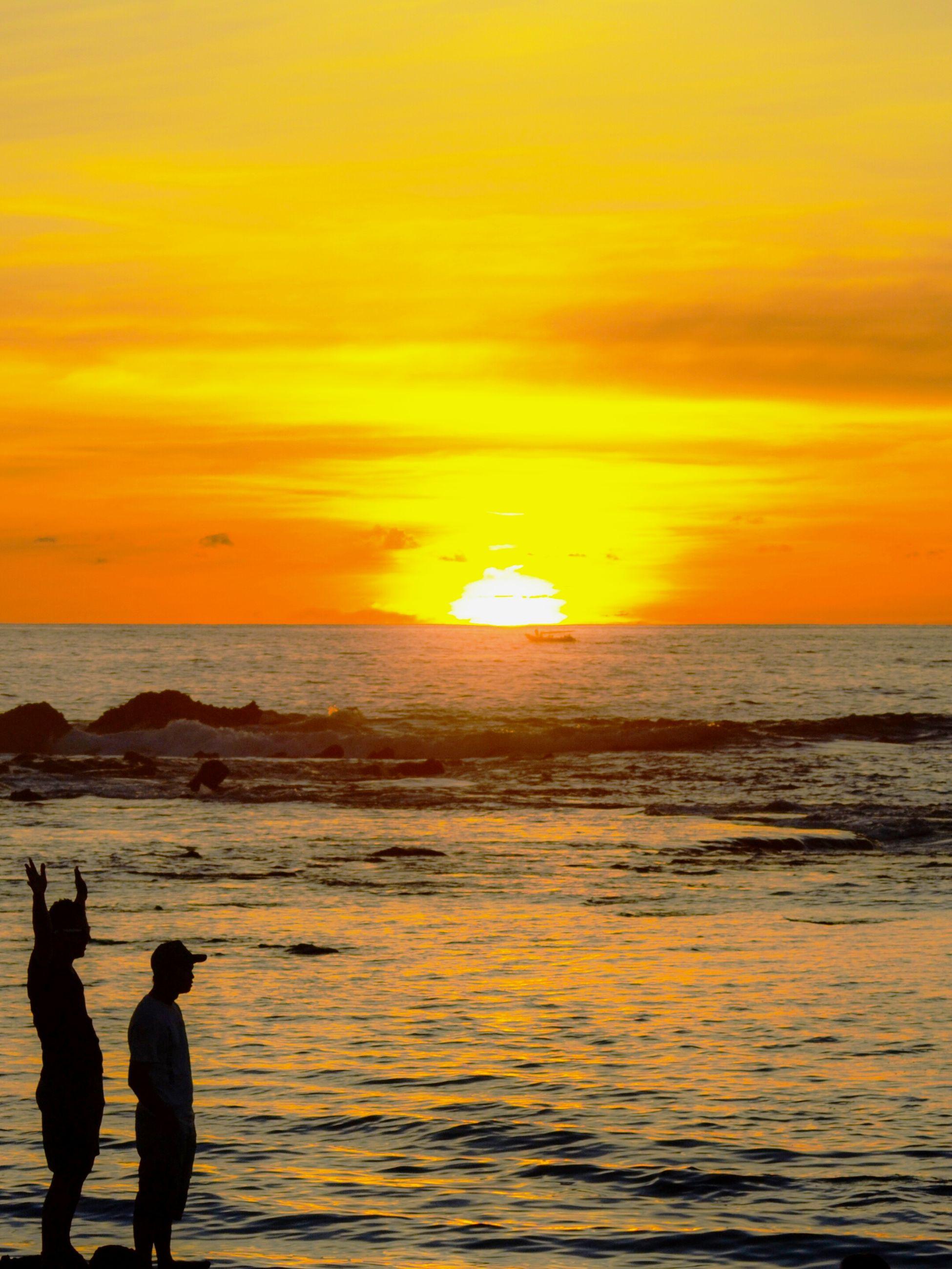sea, horizon over water, sunset, water, scenics, sky, beach, beauty in nature, orange color, silhouette, leisure activity, tranquil scene, lifestyles, tranquility, sun, idyllic, men, shore, nature