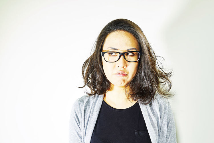 Asian woman, angry look Adult Adults Only Anger Broken-hearted Close-up Disbelief Distrust Distrustful Lady Eyeglasses  Females Front View Grieved Long Hair Looking At Camera One Person One Young Woman Only People Portrait Sad Sad Woman Studio Shot White Background Young Adult Young Women