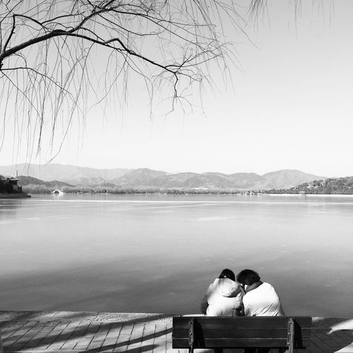 Rear view of man sitting on bench by lake