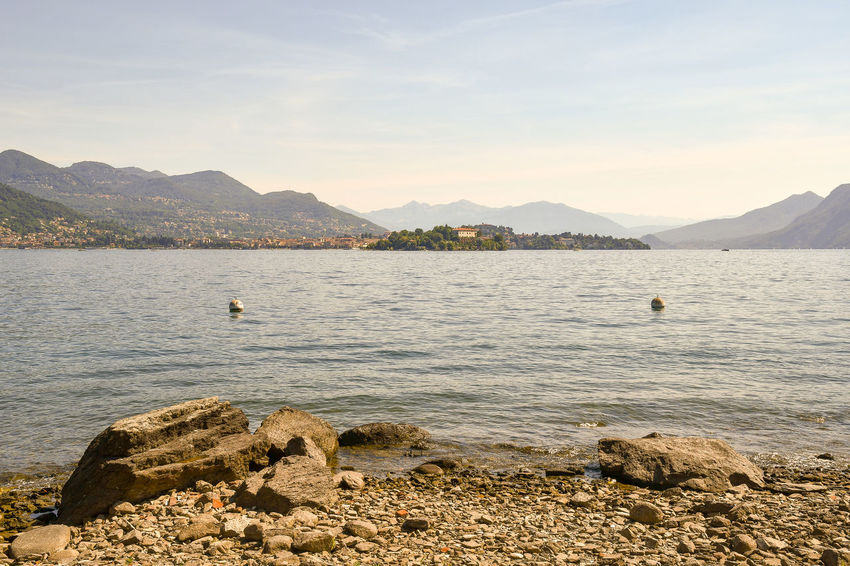 Lake view from a pebbled beach with island and coast in the background, Maggiore Lake, Piedmont, Italy Water Mountain Scenics - Nature Beauty In Nature Tranquility Rock Nature Tranquil Scene Mountain Range No People Outdoors Bay Lake Maggiore Lake Isola Madre Piedmont Italy Italy Coast Lake Beach Beach Pebbles Scenic View Travel Vacations Calm Water