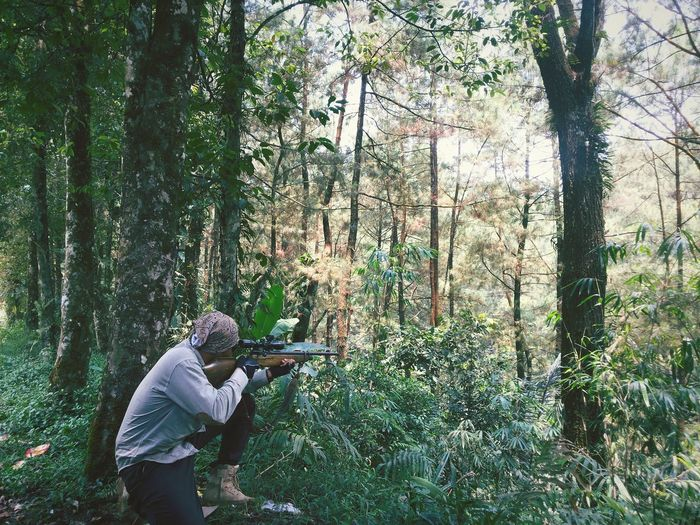 Man aiming rifle while crouching in forest