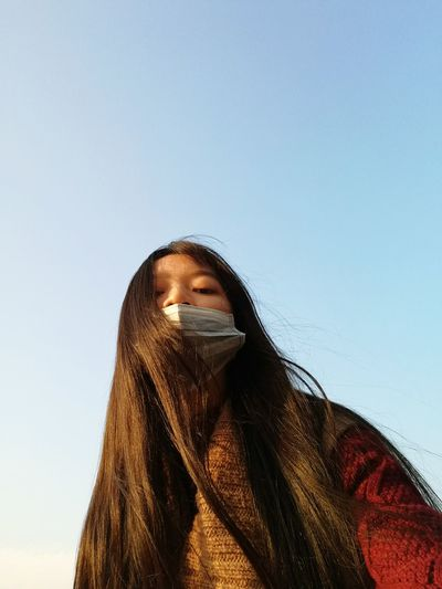 Portrait of woman wearing surgical mask against clear blue sky