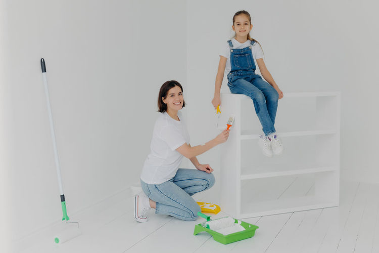 Portrait of smiling mother and daughter sitting with equipment against wall