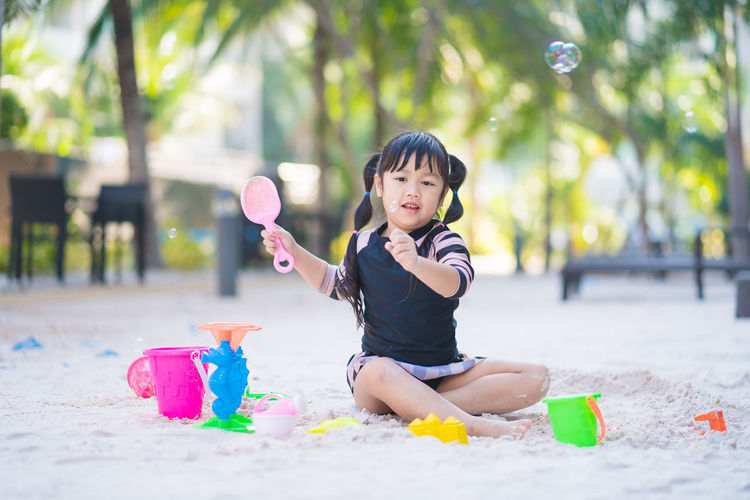 Cute boy playing with toy sitting outdoors