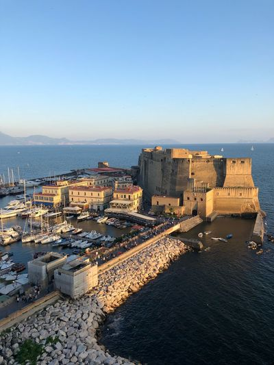High angle view of buildings and castle by sea against blue sky