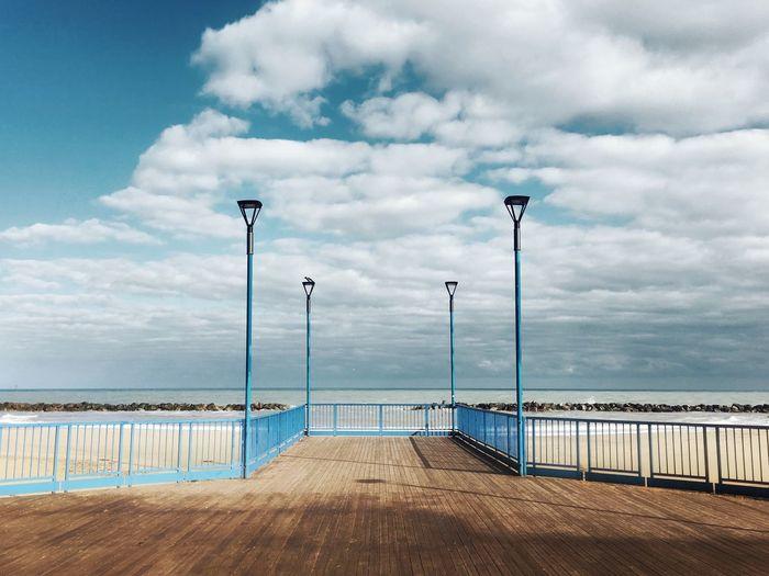 Empty pier by sea against sky