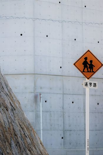 Close-up of children crossing road sign against wall
