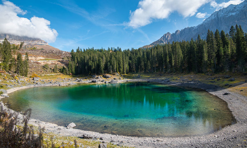 Lake carezza with deep blue colored water and the dolomite mountain range in italy, europe.