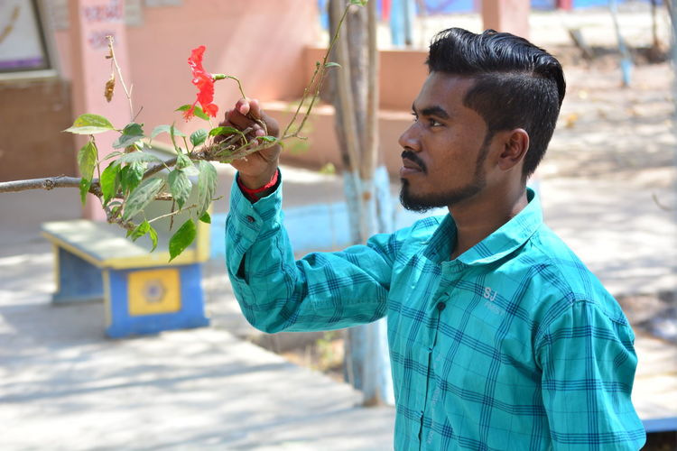 Young man holding flowering plant