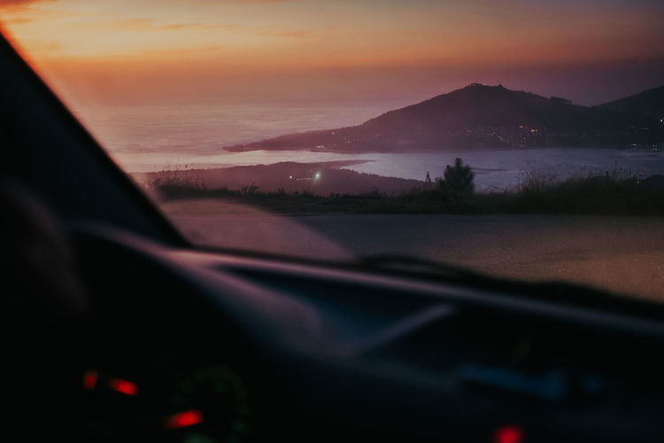 Scenic view of sunset seen through car windshield