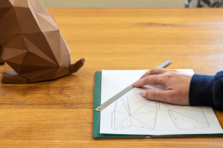 High angle view of man holding paper on table