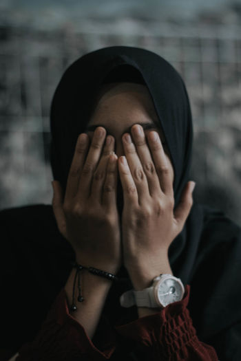 Close-up of woman wearing hijab covering face with hands